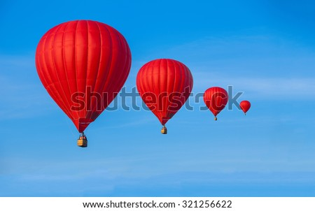 Four Red hot air balloons in blue sky with white clouds