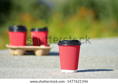 Four red paper coffee cups with black lids on a stand stand on a concrete surface on a blurred background of green trees, one of them stands separately and in front