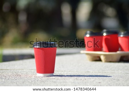 Four red paper coffee cups with black lids on a stand stand on a concrete surface on a blurred background of green trees and city, one of them stands separately and in front