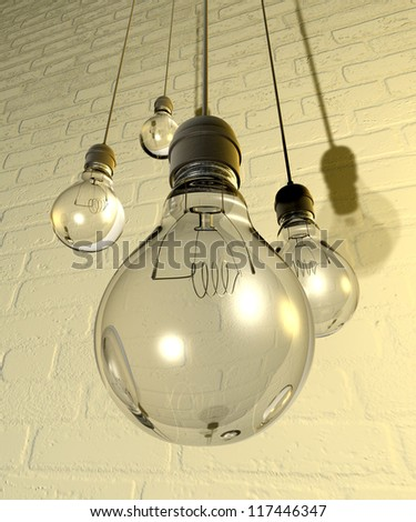 Four regular unlit light bulb fitted into light fittings hanging from chords on a white washed brick wall - stock photo