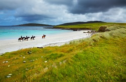 Four riders and horses on the Sellerna beach, Cleggan, in summertime, Ireland.