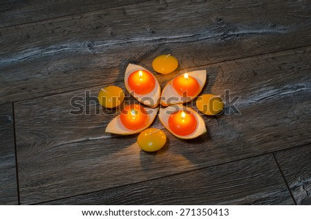 four round orange candle burning in the stands of the orange peel