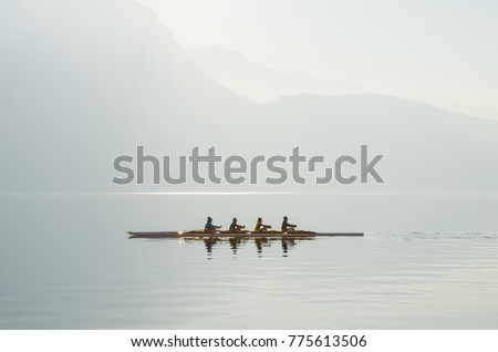 Four rowers on boat floating on sunny morning on background of mountains on lake of Lugano. Concept of healthy lifestyle, water sports. Switzerland.