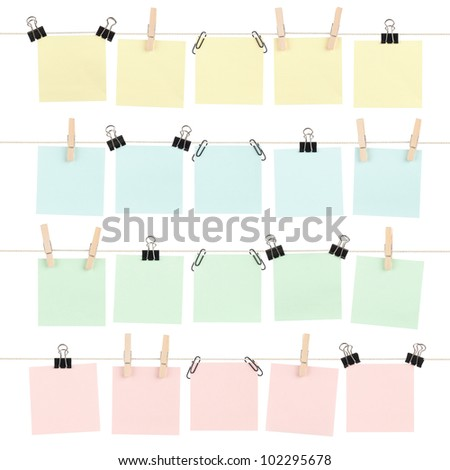 Four rows of colored blank sticky notes held on strings by various clips isolated on white.