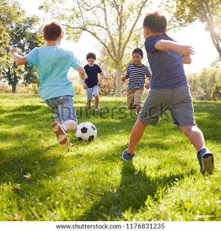 Four schoolboys playing football in the park, square format