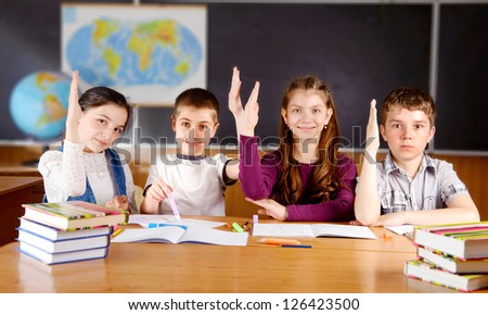Four schoolchildren aged 11 at the desk in classroom