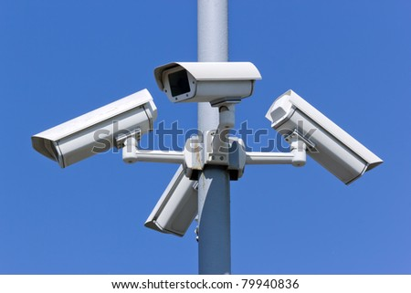 four security cameras on blue sky