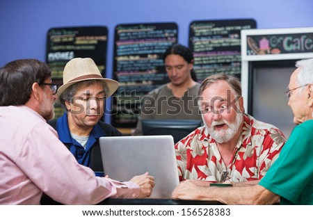 Four serious mature men in cafe with laptop