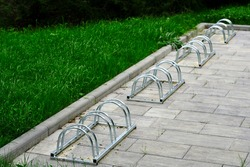 Four shiny stainless steel bicycle stands, on gray interlocking tiles