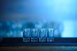 Four shots of tequila on a wooden table bar on the background of bright lights of the bar