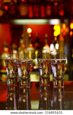four shots of tequila with lime and salt on a wooden table bar on the background of bright lights of the bar