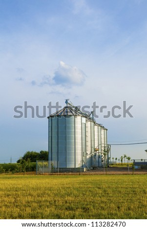 four silver silos in corn field with clouds