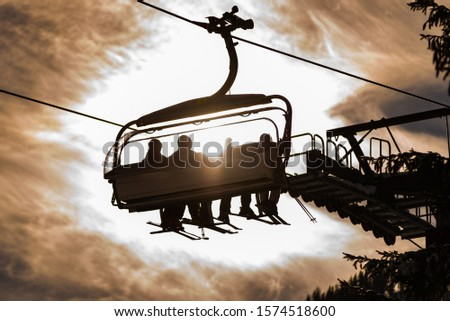 Four skiers on a chair lift against the backdrop of the sun, cloudy sky and snow covered trees, contour photo, orange shades, ski region Schladming Dachstein, Styria, Austria, Europe #1574518600