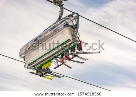 Four skiers on a chair lift against the blue sky, seen from below, from the ski slope. Ski resort Schladming Dachstein, Styria, Austria #1574518360