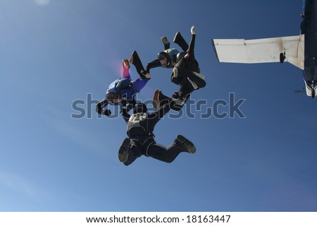 Four skydivers exit a plane as a formation