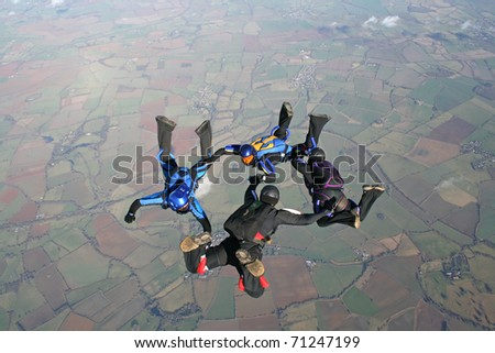 Four skydivers practicing their formations