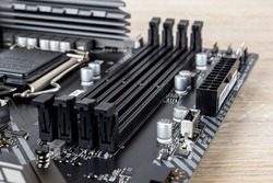 Four slots for ddr4 ram memory modules on a modern black pc motherboard. Computer mainboard circuit components. Desktop hardware close-up.  PC components for assembly, upgrade and repair. Front view.