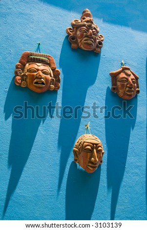 Four small ceramic masks hanging on a bright blue wall with long shadows from the equatorial sun.