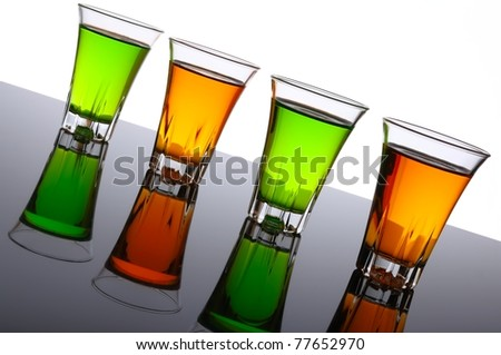 Four small shot glasses of alcoholic beverages