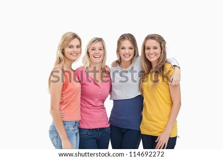 Four smiling friends as they stand beside one another