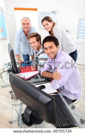 Four smiling people gathered round a computer in a classroom - stock photo