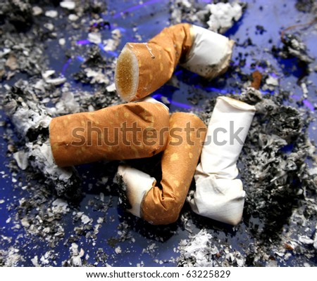 Four smoked cigarettes in a dirty ashtray