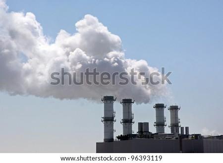 four smokestacks against blue sky producing smoke and steam energy