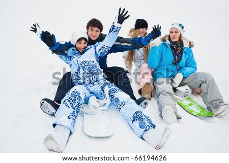 Four snowborders sit on snow and preparing to ride from the hill