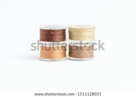 Four spools of brown and beige mixed  threads prepared for the sewing machine, isolated on white, side view  #1511128031