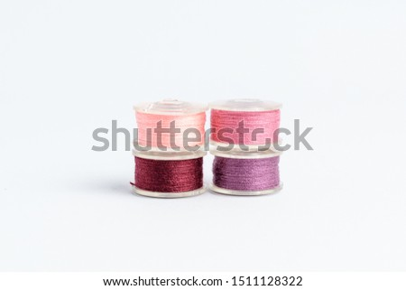 Four spools of burgundy, light pink, pink and  mauve threads prepared for the sewing machine, isolated on white, side view  #1511128322