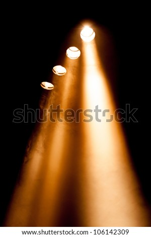 Four spotlights with orange beams in a receding line shining in a smoky atmosphere at night - stock photo