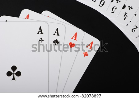 Four spread aces and additional playing cards in the right corner on black background