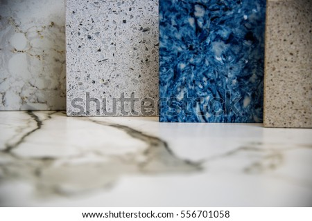 Four square stone color samples, on a white marble counter top. The samples are light brown, blue, white and greenish. Position horizontal, close-up, no background. #556701058