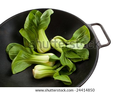 Four Stalks of baby bok choy in a black wok