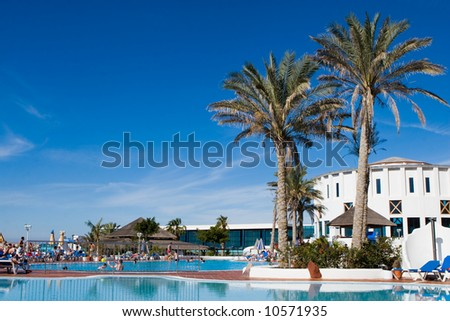 Four star hotel with swimming pool and tourists - stock photo