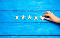 four stars and heart on a blue background. rating five stars, the choice of the editorial office and the buyer. concept of rating, review. quality, service