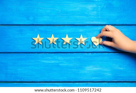 four stars and heart on a blue background. rating five stars, the choice of the editorial office and the buyer. concept of rating, review. quality, service #1109517242