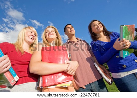 Four students carrying books and standing outside smiling. There is one boy and three girls. Horizontally framed photo. - stock photo
