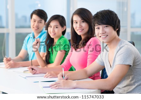 Four students sitting in classroom, the focus is on boy