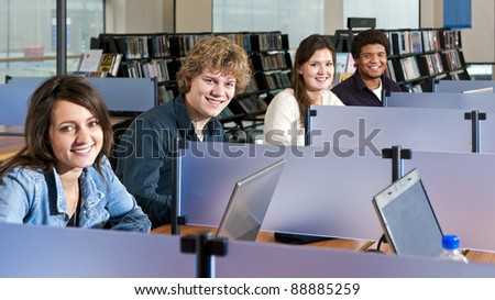 Four students studying in cubicles in a public library, with focus on the second young adult man