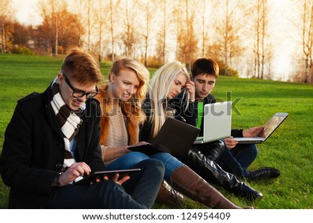 Four students, two couples working on laptops in the spring evening park