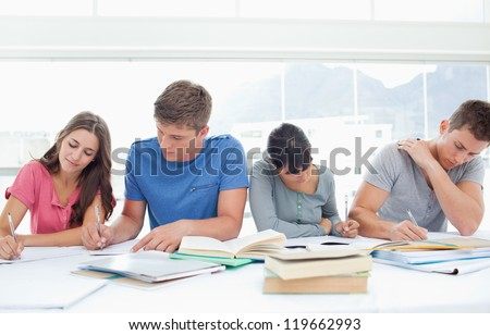 Four studying students sit beside each other and work hard