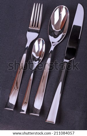 Four subjects silverware set on black fabric