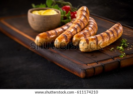 Four succulent grilled pork sausages served with a mustard dressing and fresh herbs on an old vintage wooden chopping board with copy space