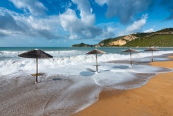 Four sun umbrellas on a golden beach (Saint George, Corfu)