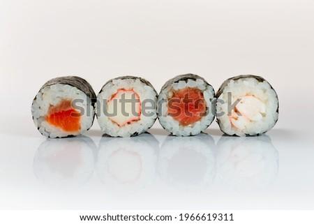 Four sushis on a white background Ebi Maki, Kani Maki Sake Maki Maguro maki.