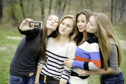 Four teen girls pretty young women taking selfshot or selfy picture of themselves happy smiling having joyful time & fun outdoors portrait