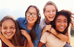 Four teenage girls having fun piggybacking outdoors