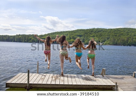 holding hands jumping. stock photo : Four teenage girls jumping off a dock at a lake, holding hands