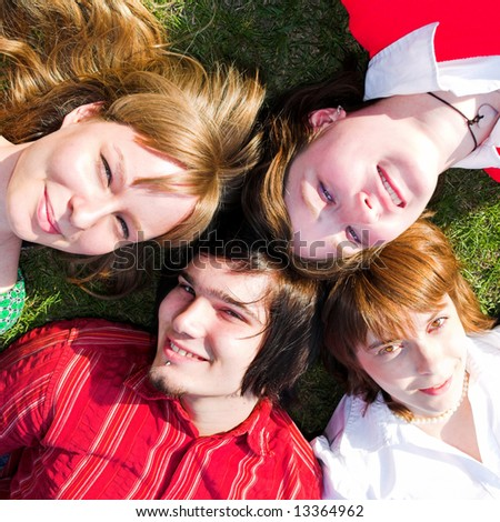 stock photo : Four teenager lay on green grass